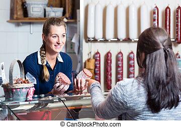 Sales lady in butchery shop serving customer