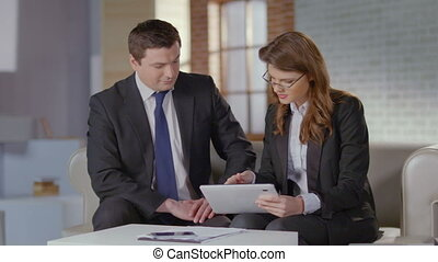Sales manager shows charts to business client on tablet, slow-mo