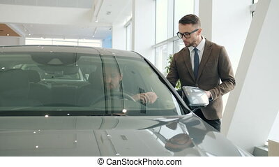 Sales manager friendly young man is talking to male client sitting in car in showroom choosing automobile holding steering wheel. People and business concept.