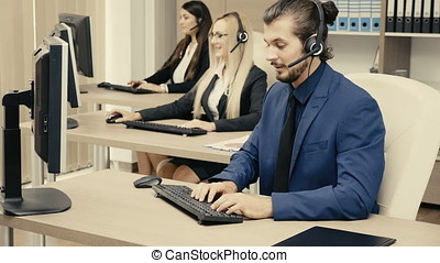 Sales marketing team in the office talking on the headphone set