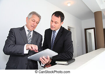 Sales people working on electronic tablet