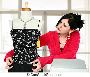 Sales Person - Young woman at cash register adjusting dress...
