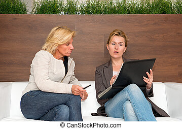 Sales pitch - Sales woman showing a product portfolio to a...