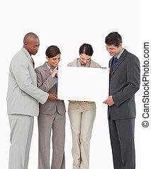Sales team holding blank sign together