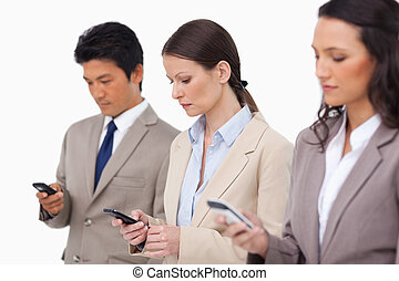 Sales team looking at their cellphones against a white...