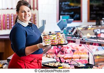Sales woman in butcher shop offering finger food
