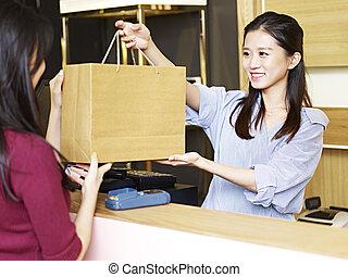 salesclerk, giver, merchandise, til, kunde