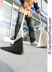 salesclerk of convenience store cleaning up