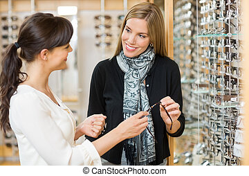 Salesgirl And Customer Holding Glasses In Shop - Young...
