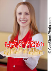 Salesgirl with Swiss cheese on a plate for tasting