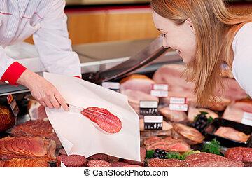 Saleslady serving sliced salami on a sheet of tissue paper...