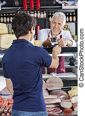Salesman Accepting Payment From Customer In Cheese Shop