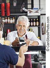 Salesman Accepting Payment From Customer Through Credit Card