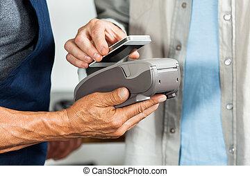 Salesman Accepting Payment Through NFC Technology