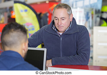 salesman and client at cash counter in hardware store