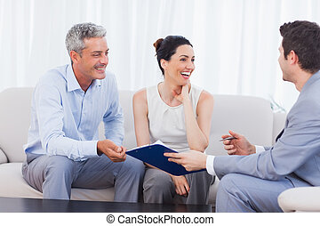 Salesman and clients talking and laughing together on sofa in home