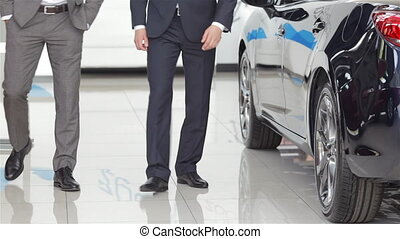 Salesman and customer in auto dealership - Seller or car...