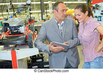 Salesman and woman in machinery store