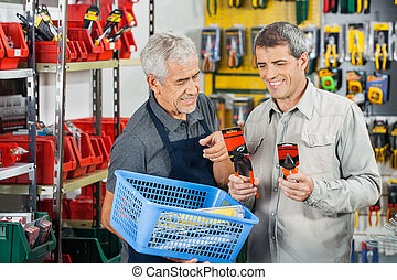 Salesman Assisting Customer In Buying Pliers