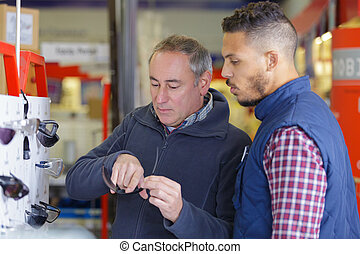salesman assisting customer in buying product at hardware store