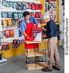 Salesman Assisting Man In Buying Tools At Store