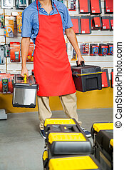Salesman Carrying Toolboxes In Store