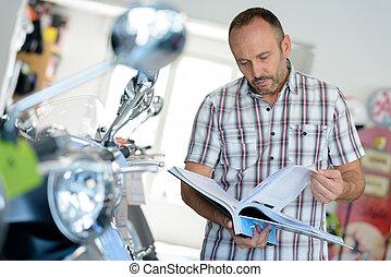 salesman checking catalogue in bike shop