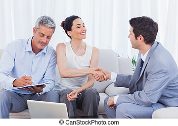 Salesman closing a deal with a couple sitting on couch