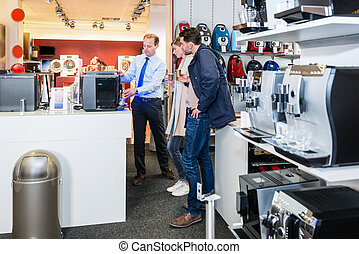 Salesman Demonstrating Coffee Maker To Couple In Store