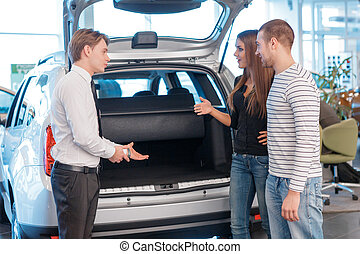 Salesman displaying trunk of the car to customers