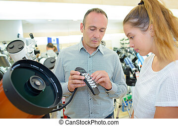 Salesman explaining controls of equipment to young lady