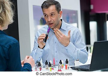 salesman explaining to customer how to use vaporizer