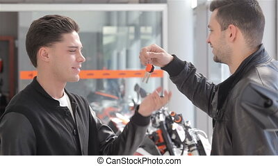 Salesman gives keys to the client - Motorbike dealer putting...
