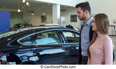 Salesman gives the car key to the couple at the dealership -...