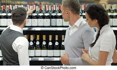 Salesman giving advice on buying bottle of wine