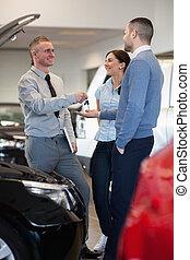 Salesman giving car key to a couple