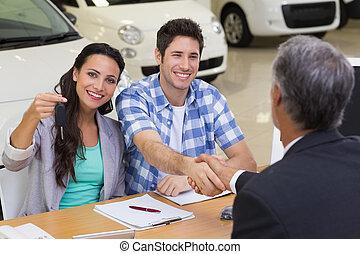 Salesman giving car keys to a couple