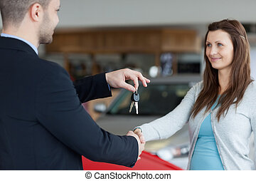 Salesman giving car keys while shaking hand of a woman