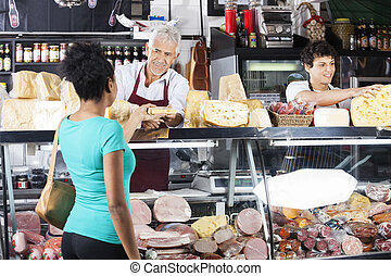 Salesman Giving Cheese To Female Customer At Counter