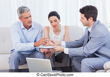 Salesman giving contract to client and his wife sitting on...