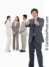 Salesman giving thumbs up with colleagues behind him