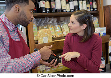 salesman giving woman advice on buying bottle of red wine