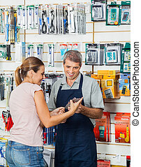 Salesman Guiding Customer In Hardware Store