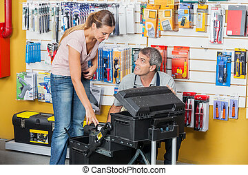 Salesman Guiding Customer In Selecting Tools At Store -...