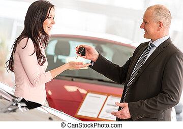 Salesman handing car keys to woman