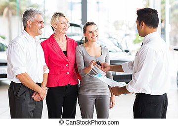 salesman handing over car key to customer