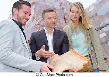Salesman holding a modern rooftile for couple to see