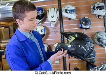 Salesman holding crash helmet