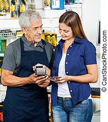 Salesman Holding Electronic Reader While Customer Paying Through