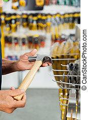 Salesman Holding Hammer In Hardware Store